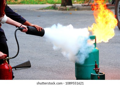 Firefighter teaching woman or man how to using fire extinguisher spraying form to fire burning on gas container