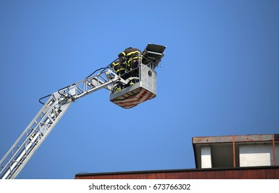 Firefighter team as they help the wounded with the stretcher fixed above the fire truck's metal basket