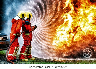 firefighter training., fireman using water and extinguisher to fighting with fire flame in accident car on the wayside road., under danger situation all firemen wearing fire fighter suit for safety.