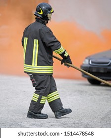 firefighter with uniform and helmet and a broken car after the road accident