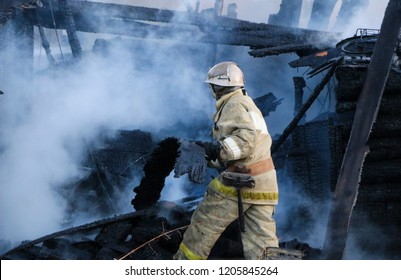 firefighter in uniform, helmet and special oxygen mask for breathing, gas mask and balon with compressed air, working after a fire.