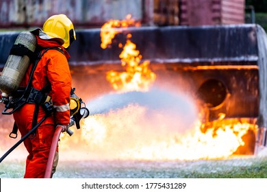 Firefighter using Chemical foam fire extinguisher to fighting with the fire flame from oil tanker truck accident. Firefighter safety disaster accident and public service concept.