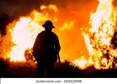 A firefighter watches as the Bobcat Fire burns in Juniper Hills, California, Saturday, Sept. 19, 2020.