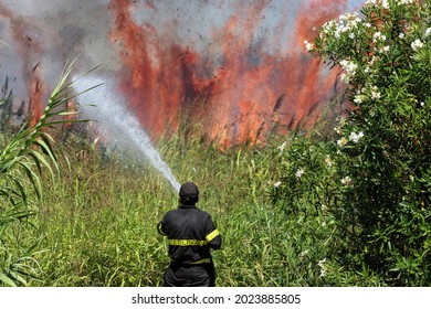 Firefighter with water extinguisher to fight fire flame in an emergency situation. Italy. Sardinia. Sicily. Greece, Turkey. Climate change. Enviromental