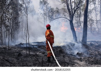 firefighter with water and fire extinguisher to fight with fire flame in an emergency situation., in danger situation all firefighters wearing firefighter suit for safety. Sardinia, italy