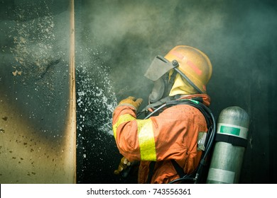 a firefighter water spray by high pressure nozzle to fire inside house surround by smoke with copy space in cinematic tone