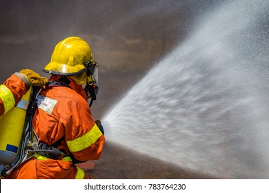 firefighter water spray by high pressure fire hose with copy space