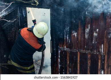 Firefighter work concept. Firefighter are using water in fire fighting operation. Real brave hero combat the fire with foam extinguisher. Brave firefighter saving burning building