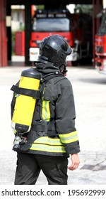 firefighter with yellow  oxygen cylinder and the helmet walks towards the fire