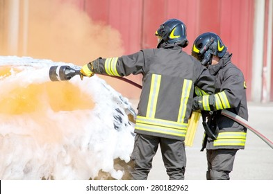 firefighters in action with foam to put out the fire of the car