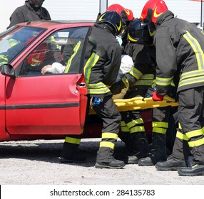 firefighters in action and pull the injured from the car after the road accident