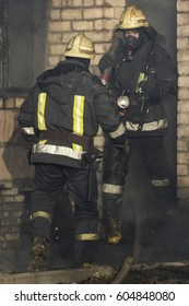 Firefighters are busy to extinguish a fire in a house