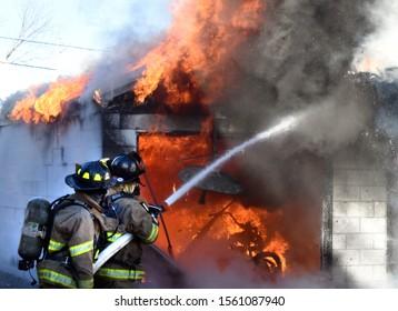 Firefighters fight a garage fire