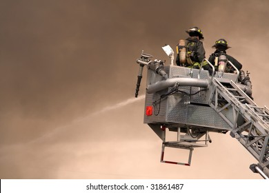 Firefighters fighting fire from bucket atop a fire truck.