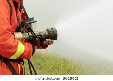 Firefighters fighting fire with pressured water during training