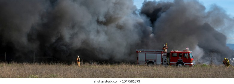 Firefighters and fire truck fighting a large brush fire with billowing smoke