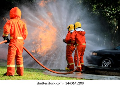 Firefighters, Firemen spraying high pressure water or suitable extinguishing agents to fire with copy space .
