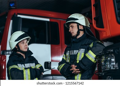 firefighters in fireproof uniform and helmets looking at each other at fire station