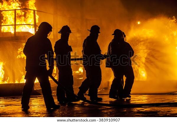 Firefighters hosing down fire