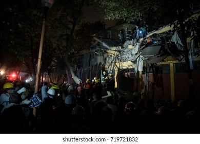 Firefighters in the night climbing the ladder to remove rubble and help finding missing persons. Mexican tragedy in the earthquake of september 2017.