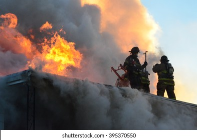 Firefighters on the roof of a house that is on fire