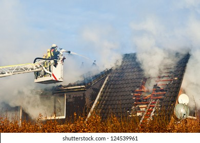 Firefighters on turntable ladder at house fire