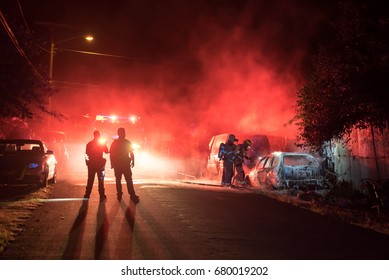 Firefighters and police officers extinguish a vehicle fire in the middle of the night.