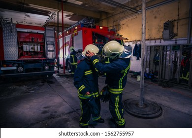 Firefighters preparing their uniform and the firetruck in the background inside the fire station