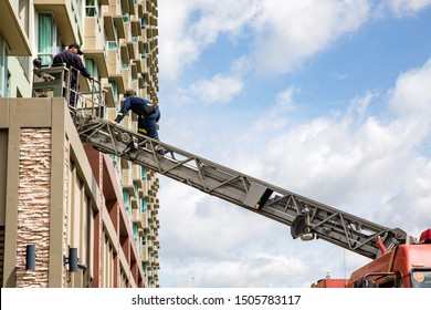 Firefighters rescue people in high building to escape by extended ladder crane of fire truck, fire drill