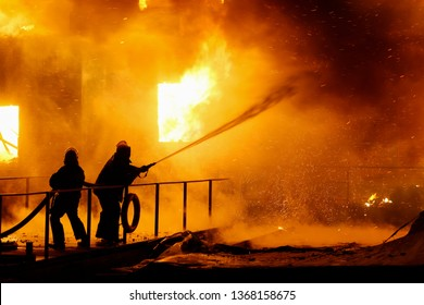 Firefighters spraying high pressure water to burning house.  Conflagration. Ukraine.
