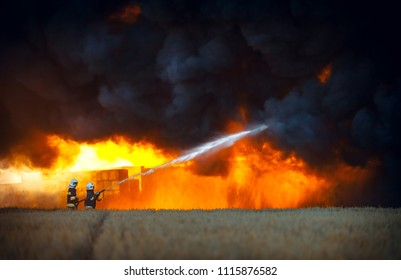 Firefighters spraying water in front of huge fire and black smoke