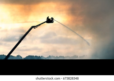 firefighters spraying water on the hay that is on fire causing big clouds of smoke