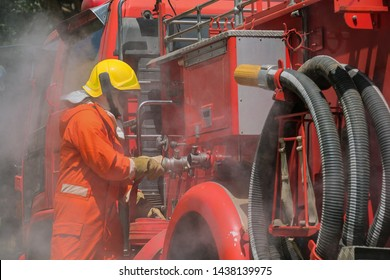 Firefighters training, Team practice to fighting with fire in emergency situation. A fireman attach hose to fire fighter vehicle