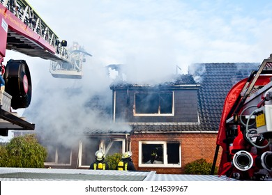 Firefighters turntable ladder at house fire