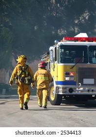 Firefighters walking toward a firetruck