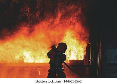 Firefighters water spray with high pressure to fire surround with damaged house, godown. Firefighter fight with the fire.