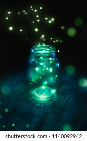 fireflies in a glass jar on a dark background