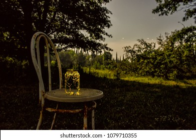 Fireflies inside a jar on an old chair outdoor