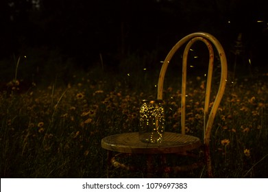Fireflies in a jar on an old chair outdoor