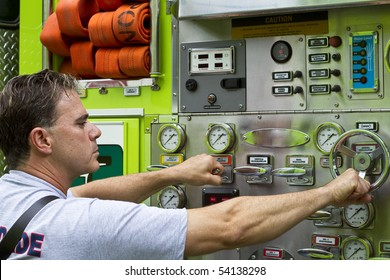 a fireman activating switches and dials on a rescue truck