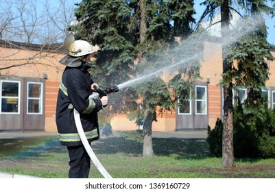 Fireman checking a firehose shooting a stream of water during training. April 5, 2019. Forestry of Sviatoshyn district, Kievskaya oblast, Ukraine