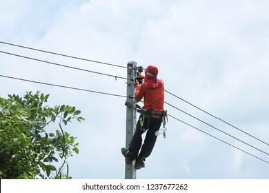 A fireman is climbing on a light pole. To install the illumination.