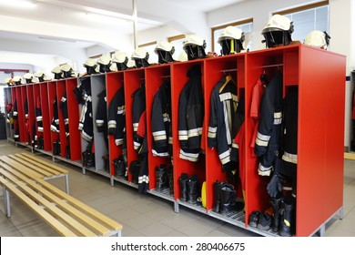 Fireman coats, helmets and boots wait for the next call. Dressing room of the volunteer fire department