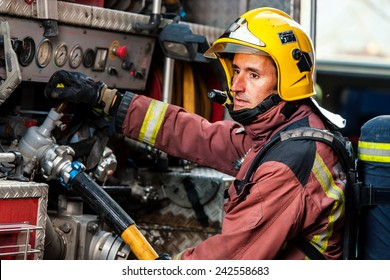 Fireman controlling water pressure at back of fire truck.