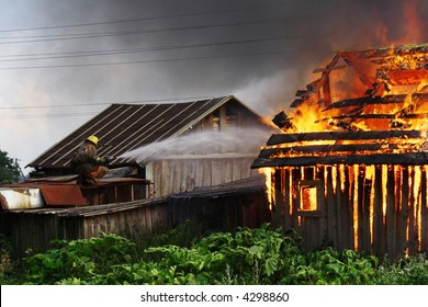 The fireman extinguishing the fire on the roof