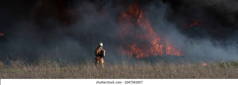 Fireman fighting large brushfire with billowing black smoke in the background