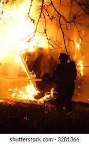 A fireman fighting a raging house fire in the middle of the night