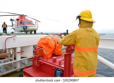 fireman is guarding for offshore helicopter before start up engine at oil rig platform in the gulf of thailand.