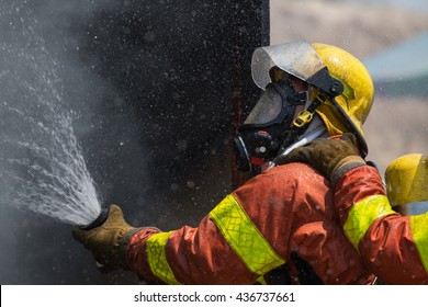fireman in helmet and oxygen mask  spraying water to fire surround with smoke and drizzle