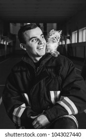 the fireman is holding a kitten